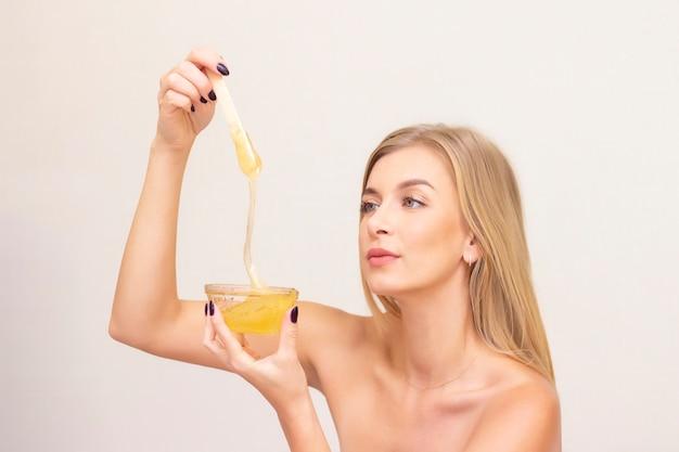Blonde girl on a shugaring procedure