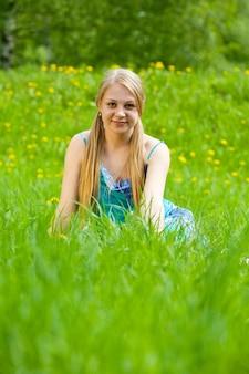 Ragazza bionda si siede in erba