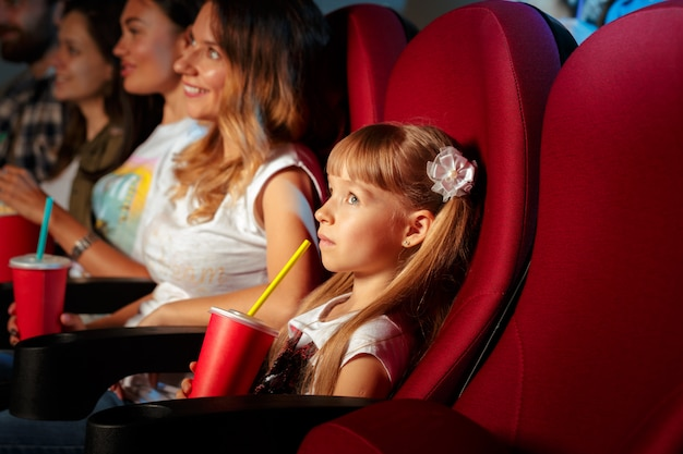 Blonde girl sitting in movie theater with popcorn and drinks
