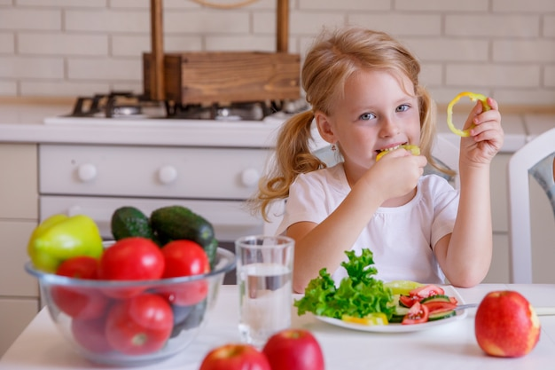 Blonde girl sitting at the table in the kitchen eating vegetables
