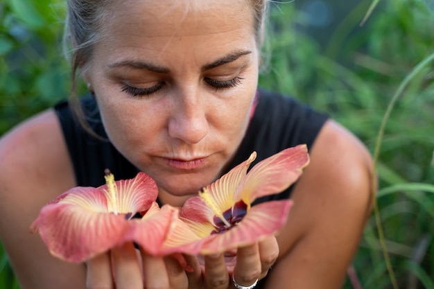 Blonde girl smelling some exotic flowers in her hands