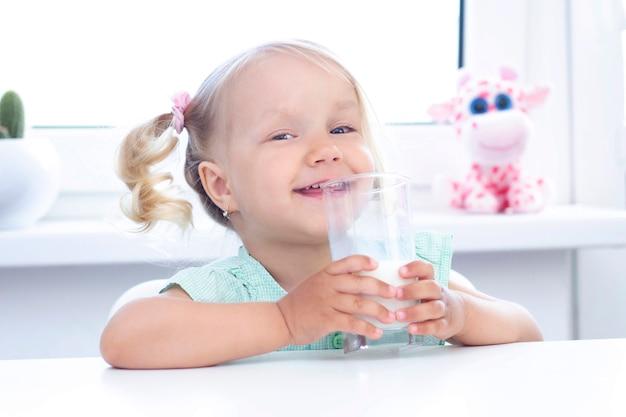 ブロンドの女の子は笑顔で牛乳を飲みます。明るい背景。