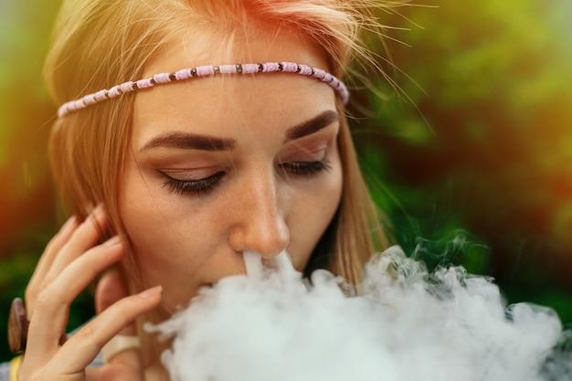 Блондинка курит электронную сигарету.
