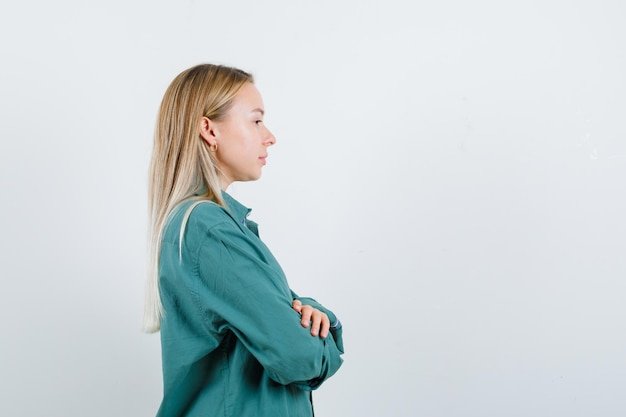 Blonde girl standing arms crossed in green blouse and looking radiant.