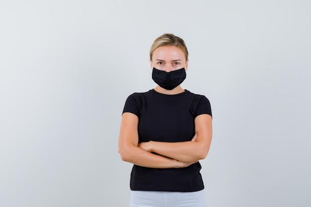 黒のtシャツで腕を組んで立っているブロンドの女の子、分離された白いズボン