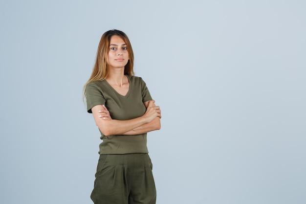 금발 소녀는 올리브 녹색 티셔츠와 바지를 입고 팔짱을 끼고 매력적인 앞모습을 보고 있습니다.