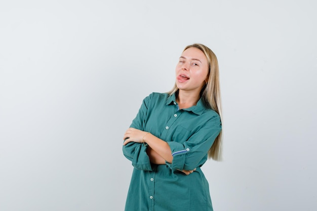 금발 소녀 서 팔 넘어, 녹색 블라우스에 혀를 튀어 나와 즐겁게 찾고