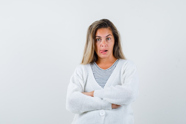 금발 소녀 서있는 팔을 넘어 줄무늬 티셔츠, 흰색 카디건 및 진 바지에 혀를 내밀고 즐겁게 찾고 있습니다.