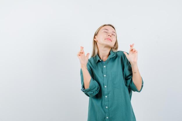 Ragazza bionda in piedi dita incrociate, chiudendo gli occhi in camicetta verde e guardando carina.