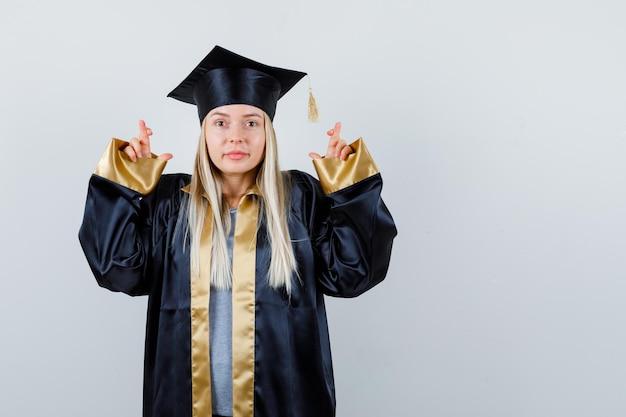 Ragazza bionda in piedi dita incrociate in abito da laurea e berretto e sembra felice.