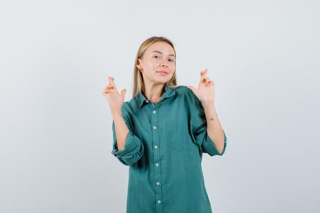 Ragazza bionda in piedi con le dita incrociate in camicetta verde e sembra carina.
