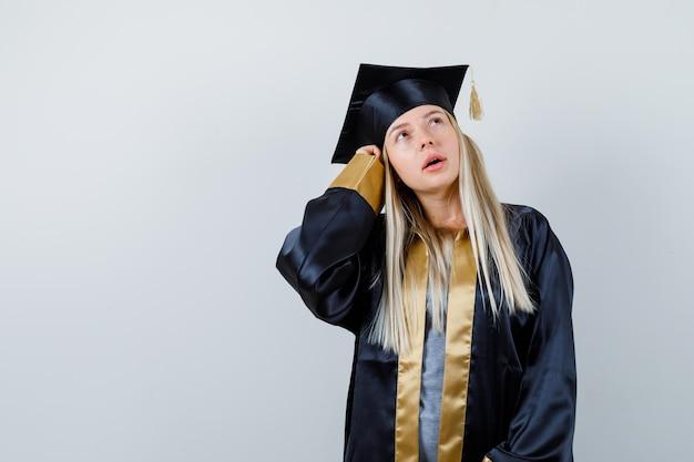 卒業式のガウンとキャップでポーズを考えて立って物思いにふけるブロンドの女の子