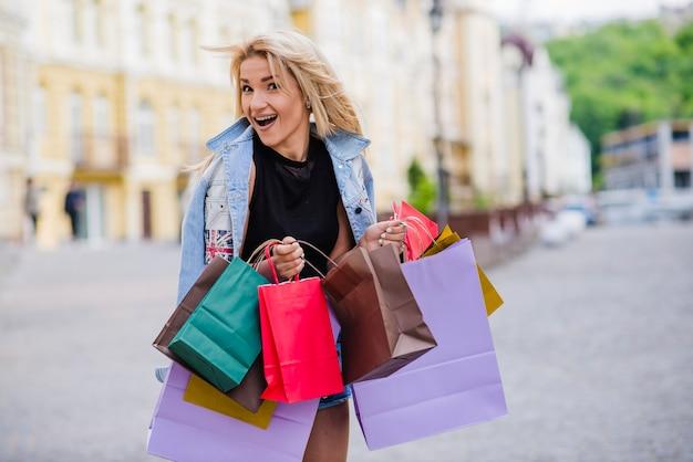 Blonde girl standing outside holding shopping bags