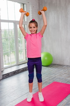 A blonde girl standing on pink carpet exercising with dumbbell looking at camera