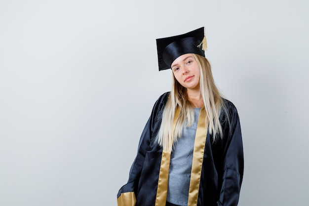 まっすぐ立って、卒業式のガウンとキャップでカメラにポーズをとって、かわいく見えるブロンドの女の子