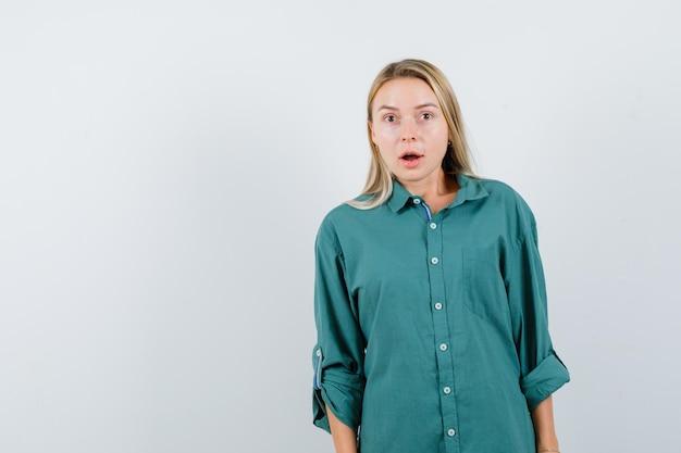 まっすぐ立って、緑のブラウスでカメラにポーズをとって、驚いて見えるブロンドの女の子