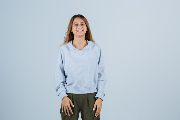 まっすぐ立って、オリーブグリーンブルーのスウェットシャツとパンツでカメラに向かってポーズをとって、魅力的な正面図を探しているブロンドの女の子。