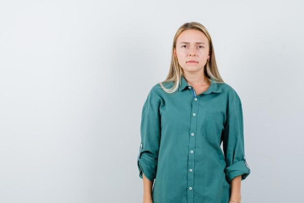 Blonde girl standing straight, biting lips and posing at camera in green blouse and looking serious.