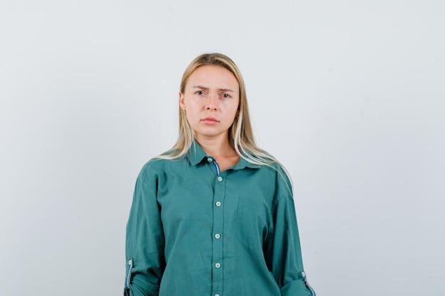 금발 소녀는 똑바로 서서 찡그린 얼굴로 녹색 블라우스에 카메라에 포즈를 취하고 불쾌감을 느낍니다.