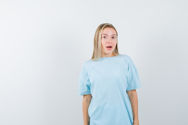 Blonde girl standing straight and posing at camera in blue t-shirt and looking pretty , front view.