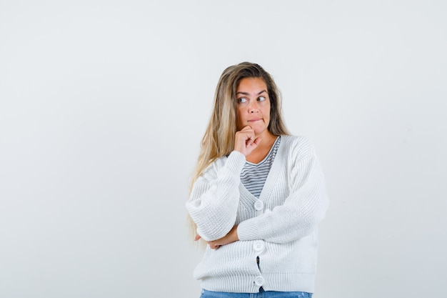 Blonde girl standing in thinking pose in striped t-shirt, white cardigan and jean pants and looking pensive. front view.