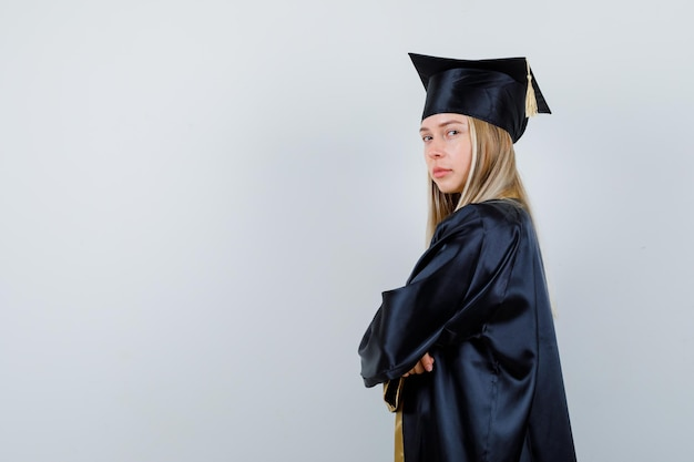 Ragazza bionda in piedi con le braccia incrociate in uniforme laureata e dall'aspetto fiducioso. .