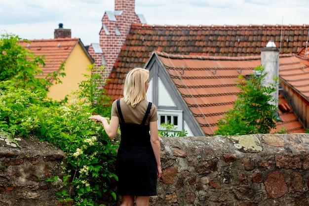 ブロンドの女の子はヨーロッパの古い都市のタイルの家の近くに滞在します。