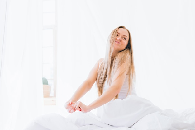 Blonde girl stretching on the bed