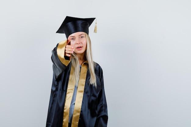 卒業式のガウンとキャップで誰かに挨拶し、愛想が良いように見えるように手を伸ばしているブロンドの女の子