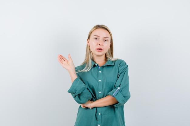Блондинка протягивает руку, приветствуя кого-то в зеленой блузке и выглядит красиво