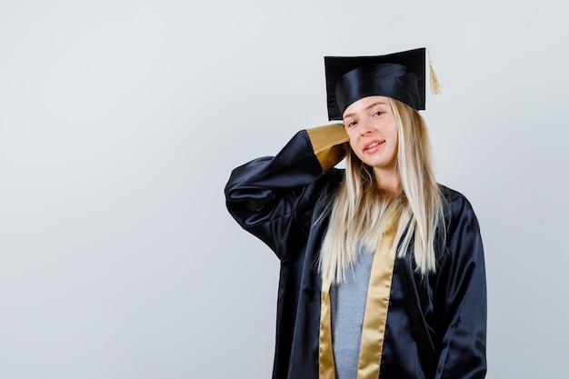 Блондинка протягивает руку за голову в выпускном платье и кепке и выглядит мило