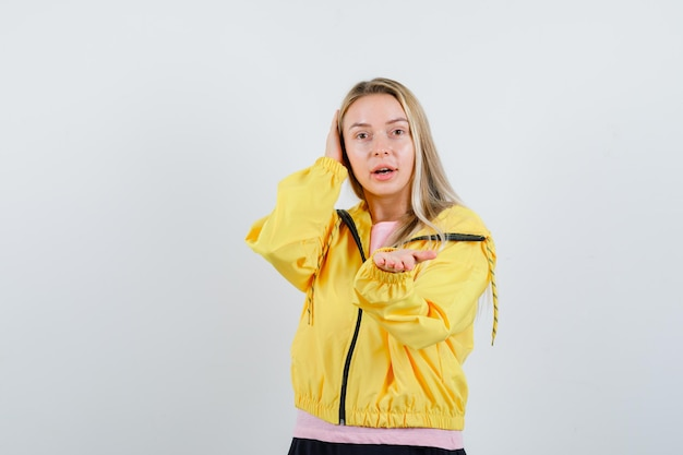 Blonde girl stretching hand to offer something in yellow jacket and looking cute.
