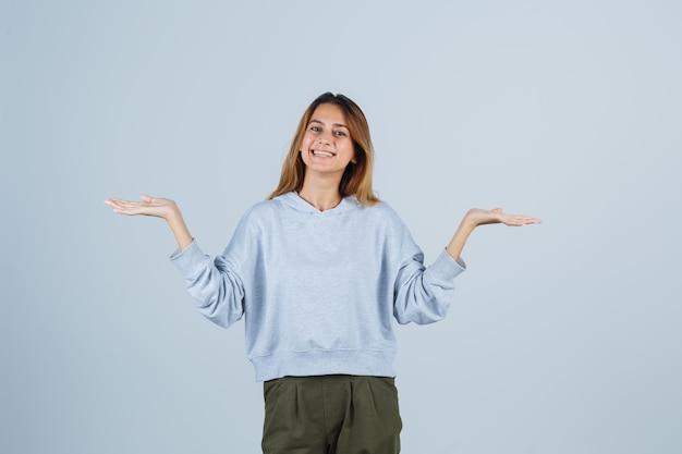 オリーブグリーンブルーのスウェットシャツとパンツで何かを持って提示し、愛想が良いように手を伸ばしているブロンドの女の子。正面図。