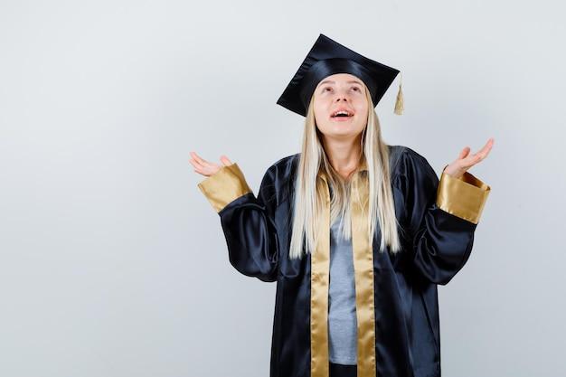 何かを持って卒業式のガウンとキャップでそれを見て、集中して見えるように手を伸ばしているブロンドの女の子
