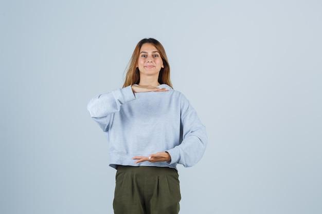 オリーブグリーンブルーのスウェットシャツとパンツで何かを保持し、陽気に見えるように手を伸ばすブロンドの女の子、正面図。