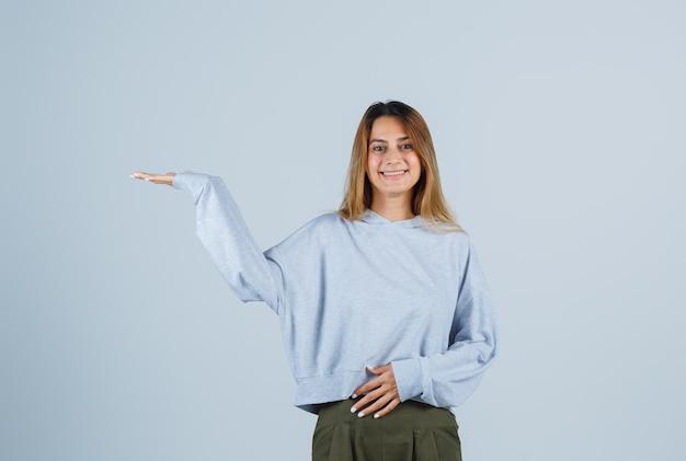 オリーブグリーンブルーのスウェットシャツとパンツで腹に片手を握り、幸せそうに見える間、何かを持っているように手を伸ばしているブロンドの女の子。正面図。