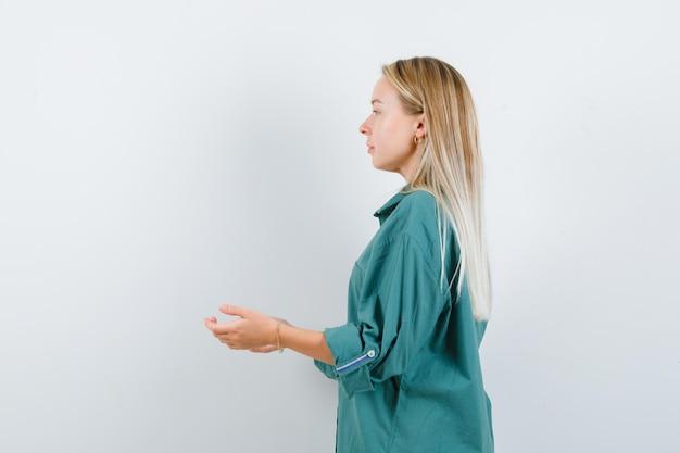 Блондинка протягивает руки, как получает что-то в зеленой блузке и выглядит красиво.