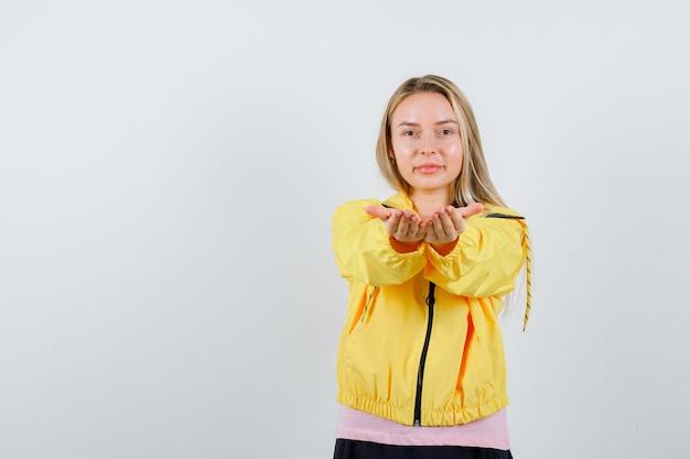 분홍색 티셔츠와 노란색 재킷을 입고 낙관적으로 보이는 금발 소녀 손을 뻗어