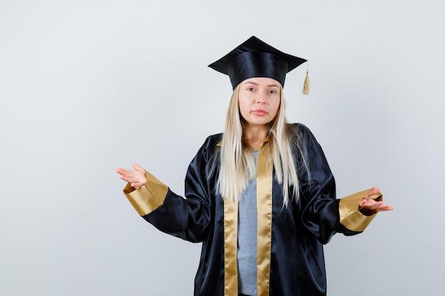 卒業式のガウンとキャップで疑わしい方法で手を伸ばし、困惑しているように見えるブロンドの女の子。