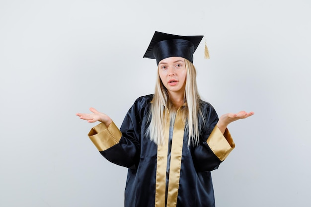 卒業式のガウンとキャップで疑わしい方法で手を伸ばして困惑しているブロンドの女の子
