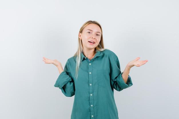 緑のブラウスで疑わしい方法で手を伸ばして困惑しているブロンドの女の子
