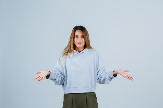 オリーブグリーンブルーのスウェットシャツとパンツで疑わしい方法で手を伸ばして困惑しているブロンドの女の子。正面図。