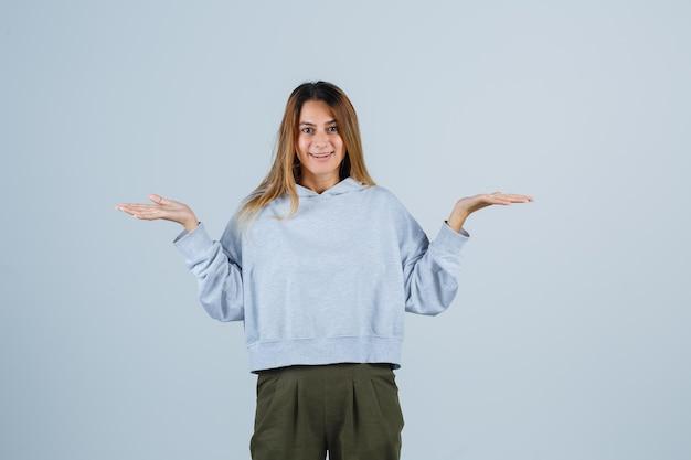 Ragazza bionda che allunga le mani in modo interrogativo in felpa e pantaloni blu verde oliva e sembra felice. vista frontale.