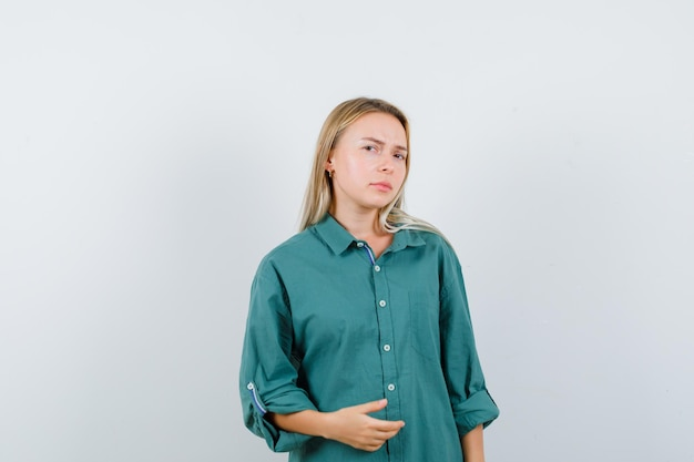 Blonde girl stretching one hand as holding something in green blouse and looking serious