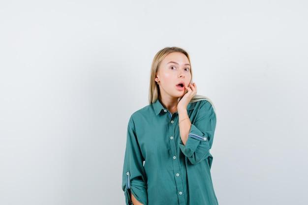 Блондинка в зеленой блузке протягивает руку ко рту и выглядит хорошенько
