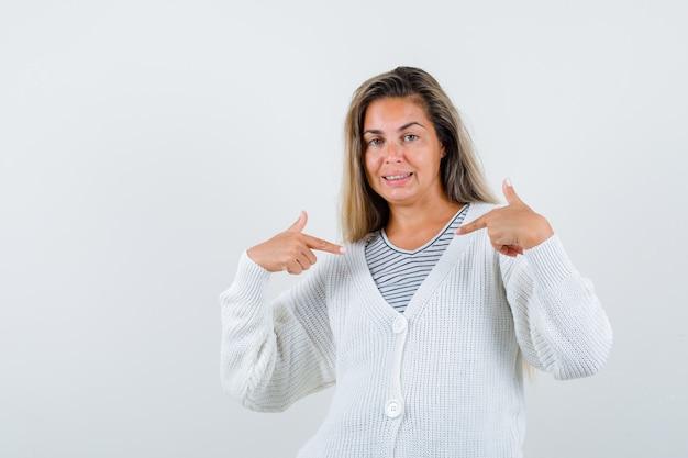 Ragazza bionda in maglietta a righe, cardigan bianco e pantaloni di jeans che punta a se stessa e che sembra felice, vista frontale.