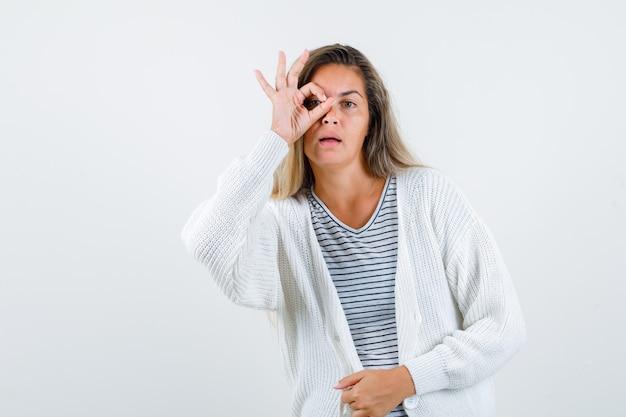 Ragazza bionda in maglietta a righe, cardigan bianco e pantaloni di jeans che mostra il segno giusto sull'occhio e sembra seria, vista frontale.