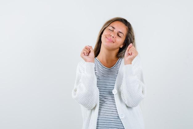Ragazza bionda in maglietta a righe, cardigan bianco e pantaloni jeans che mostra il gesto del vincitore e sembra fortunato, vista frontale.