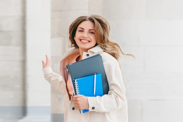 기쁨을 위해 점프 금발 여자 학생입니다. 여자는 시험, 교육 개념을 성공적으로 통과