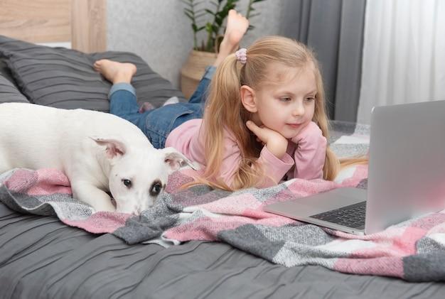 노트북으로 온라인 집에서 금발 소녀 연구. 아이들과 침대에 개.